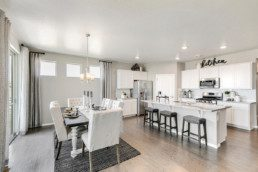 A dining and room and kitchen of a new home, decorated in white accents, featuring a large island.
