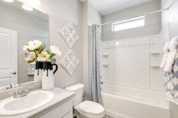 A modern bathroom decorated in white accents with a bathtub and shower combination.