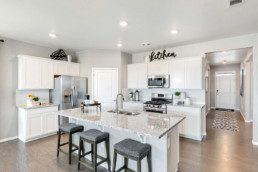 Large open concept kitchen with new appliances and an island with breakfast bar.