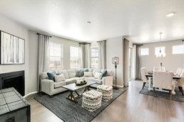 A large open concept great room with fireplace an large sectional couch.