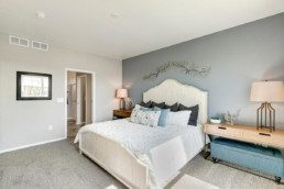 A large master bedroom with a grey wall, white bed and a beautiful metal art piece on the wall.