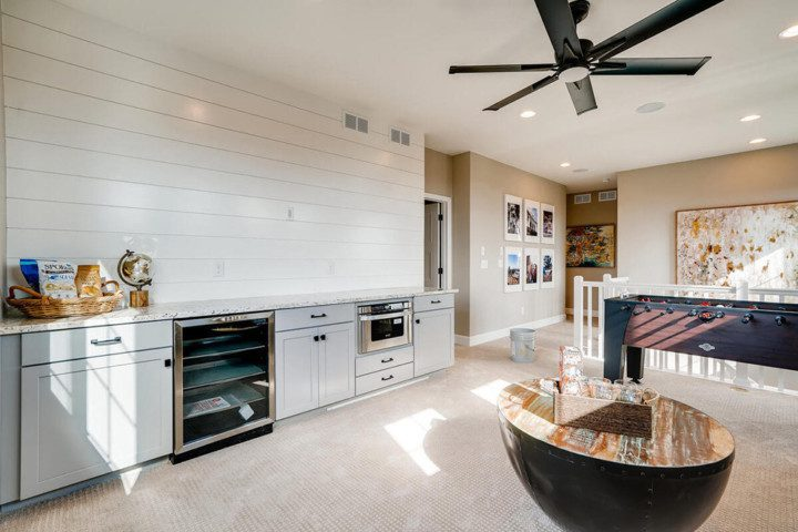 A family room featuring a wine cooler and bar counter top with a Foosball table.