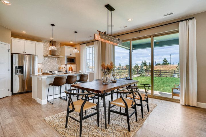 A rustic but contemporary dining room and kitchen with a large sliding glass door leading to a manicured backyard.