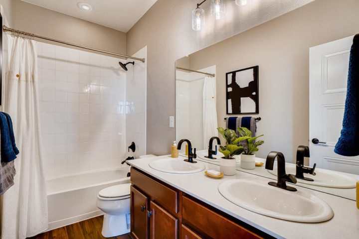 A new bathroom with double sinks, a large bathtub and shower and modern faucets.