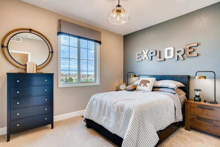 A new bedroom featuring blue accents, a large bed, artwork on the wall and a large window.