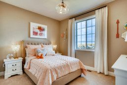 A peach colored girls bedroom with comfortable bed featuring many pillows and a large windows.