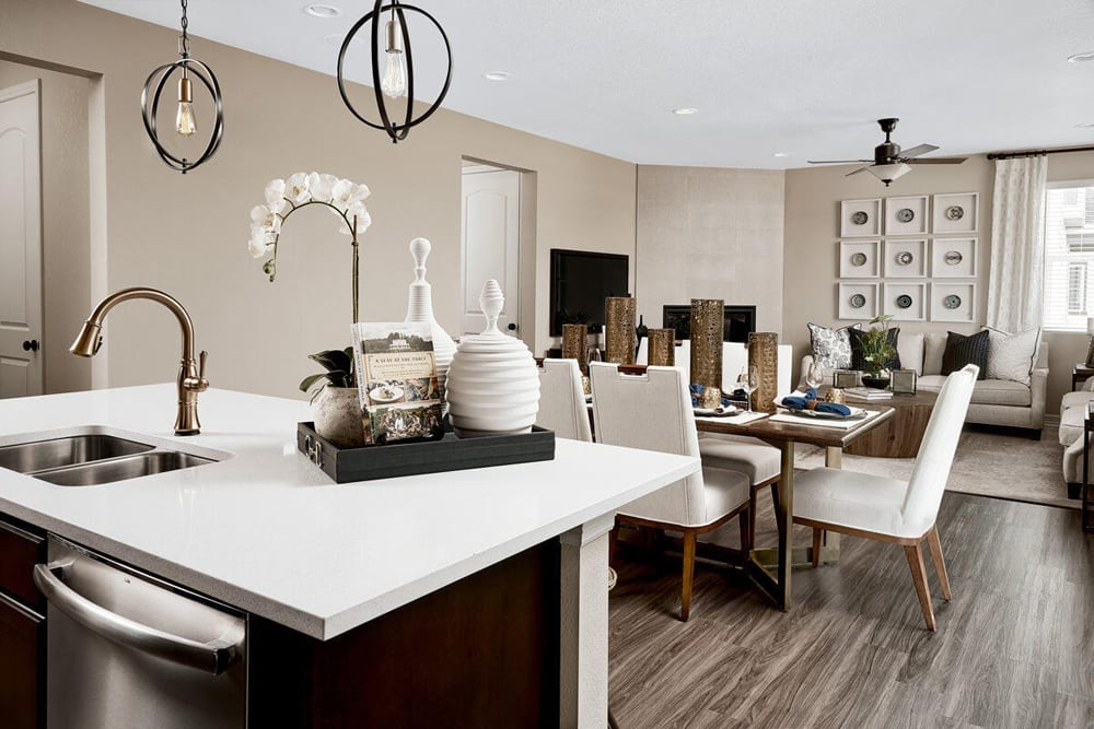 The view of a kitchen island, leading into a large dining room and great room featuring a fireplace and ample space.