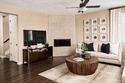 A modern family room with plush couch, large TV and a fireplace.