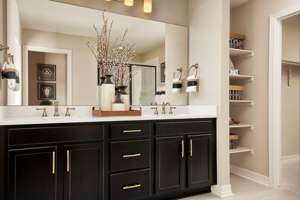 A large bathroom vanity with dark cabinetry, a white countertop and double sinks.
