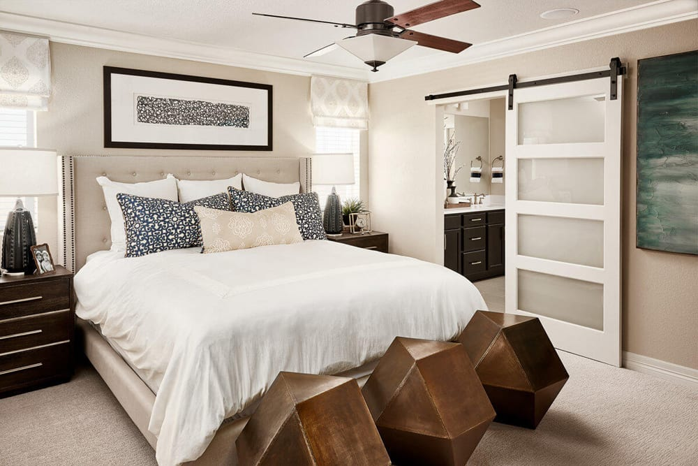 A contemporary master bedroom with large bed, and a barn door covering the ensuite bathroom.