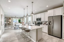 A beautiful brand new white kitchen with island and 3 stools, leading into a brand new dining room.