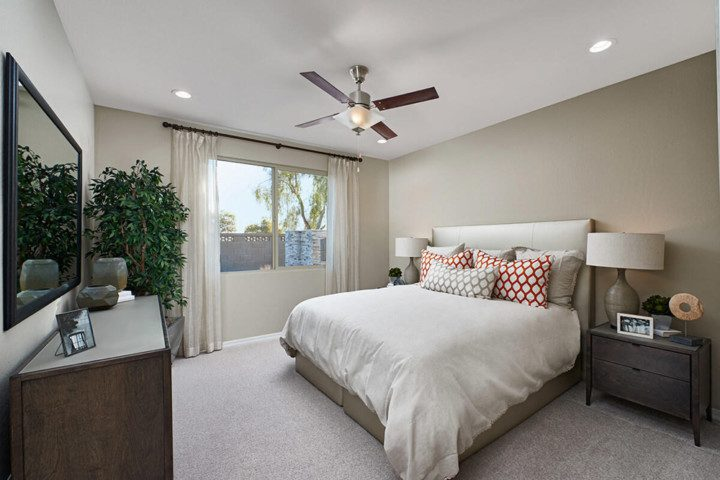 A beautiful new bedroom with a large bed, ceiling fan and a large window.