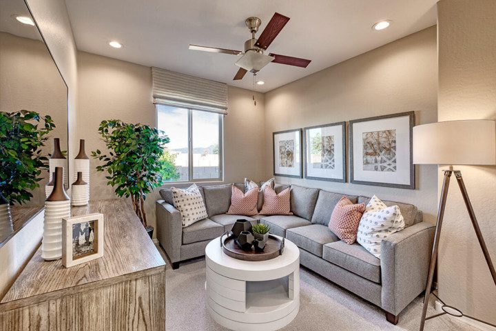 A comfortable family room with grey sectional and decorative throw pillows with a round coffee table.