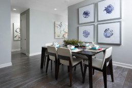 A large dining room with a modern table and colorful artwork.