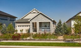 A beautiful new home with attached garage, a front veranda, and contemporary stonework on the exterior.
