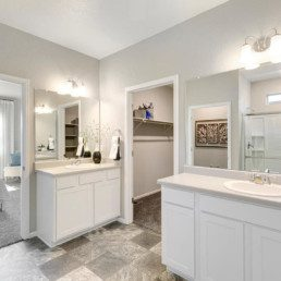 A large master ensuite featuring two vanities with two sinks an a large walk in closet.