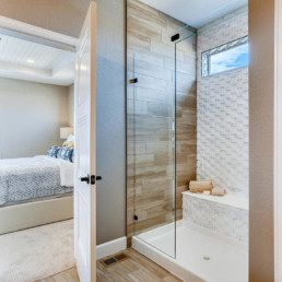 A contemporary ensuite bathroom featuring a shower with a wooden wall and white tile backsplash.