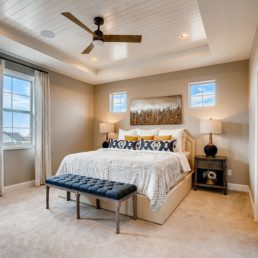 A large master bedroom with double windows and a large bed.