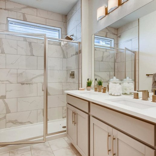 A modern bathroom with a large shower and vanity with double sinks.