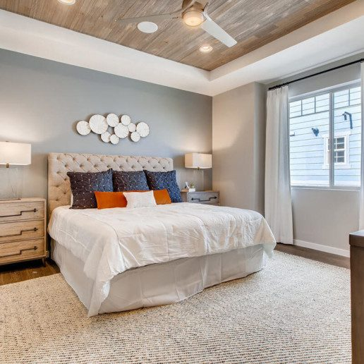 A large bedroom with a feature wall, contemporary artwork and a large bed with throw pillows.