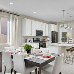 A dining room featuring ahite and orange accents on the table, leading into a brand new kitchen with white cupboards and an island.