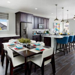 A brand new colorfully decorated dining room and kitchen featuring dark cabinetry.