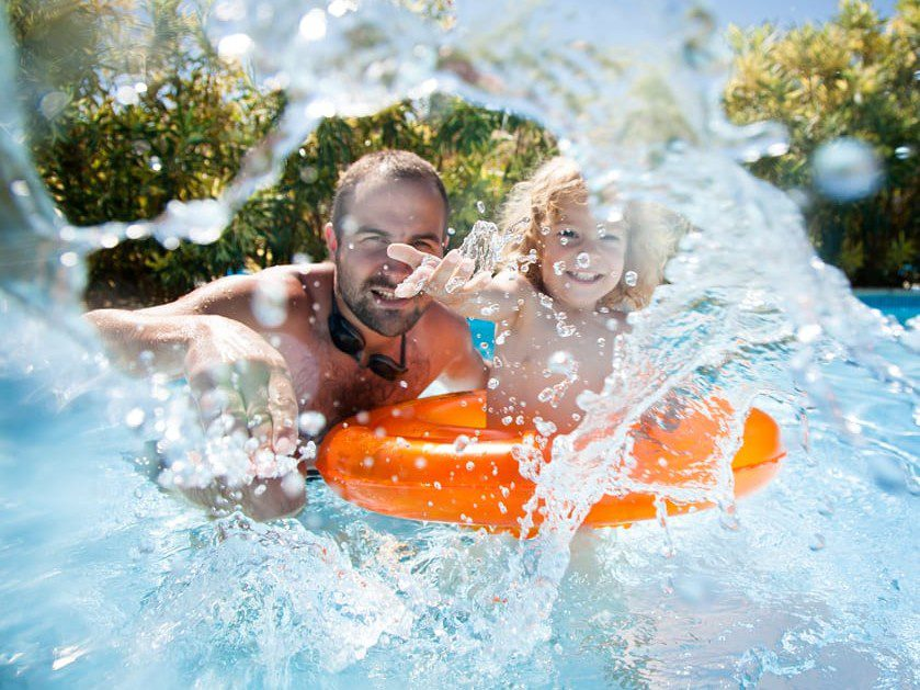 A young child with an orange inner tube and their father playing and splashing in a pool.