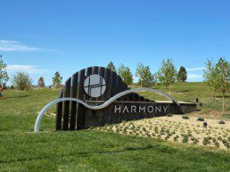 The Harmony entry feature among green grass, new trees and a freshly planted garden.